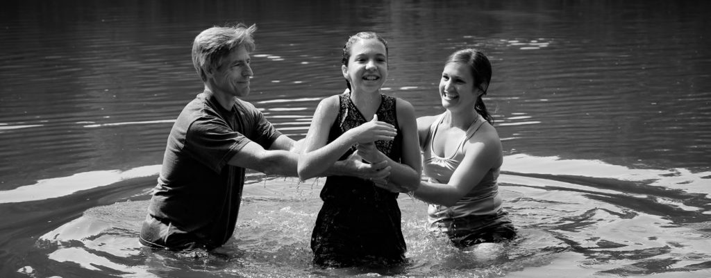 teenage girl being baptized in river